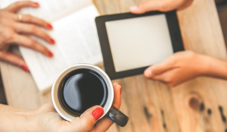 A book, e-reader, and coffee mug on a table